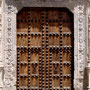 Las jambas y el dintél llevan esculpidos en bajorrelieve alternancia de cruces de Jerusalén y escudos de Mendoza entre perfiles de perlas y acanto perfilado.