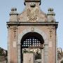 PUENTE DE ALCÁNTARA. Arco de entrada al puente, 1721. Construido en ladrillo y piedra, decorado por guirnaldas de flores y frutas, con tarjetas que portan inscripciones conmemorativas y las armas de la ciudad.