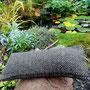 Die Füllung des handgewebten Kissens ist Wolle