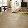 Long, plank-like porcelain tiles are set in a herringbone to create the illusion of a modernized parquet wood floor.