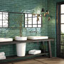 An emerald bathroom is a striking backdrop for bright white fixtures.