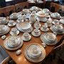 # 17 Un chic ensemble de vaisselle de 12 personnes pour les grandes occasions.Ce set de vaisselle est blanc orné de marine et d'or et comprend 10 morceaux par personne  (3 morceaux manquants seulement) et plusieurs pièces de services incluses.