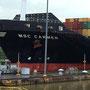 Das riesige Frachtschiff fährt zwar selbst durch die Schleuse, wird aber seitlich von Lokomotiven gesichtert, damit es bei Schrägfahrt nicht die Wände tochiert