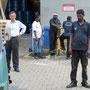 die hafenarbeiter glauben noch nicht daran, dass wir den bus in den container kriegen