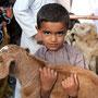 kleiner junge mit seinem geissli am viehmarkt von nizwa
