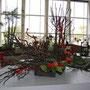 "H. Lanz, H. Lintner: Äste (verkohlt und rot lackiert), Rosen, Funkien - ""Liebe baut Brücken"""