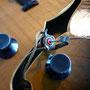 Le jack de sortie de ces guitares est vissé sur l'éclisse sans être fixé sur un cache, ce qui oblige à le sortir par l'ouïe, ici à l'aide d'une corde et d'une cheville.
