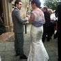 Körperbetontes Brautkleid mit Carmen-Ausschnitt aus, zum Teil in Fältchen gelegter, hell-silberfarbener Dupion-Seide dazu eine Stola aus fliederfarbener Spitze