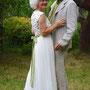 Sommerliches Brautkleid aus bestickter Orissa-Seide und leichtem Seiden-Georgette mit eingearbeiteten Gürtel, passend zum Hemd des Bräutigams. Dazu eine Rose aus roter Orissa-Seide für die Haare