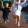 Wadenlanges Brautkleid aus Dupionseide mit blauem Gürtel aus Duchesse-Seiden-Satin. Dazu trägt die Braut einen passend angefertigten Haarschmuck und eine Clutch aus dem Duchesse-Satin genäht