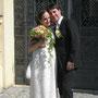 Schmal geschnittenes, romantisches Brautkleid aus edlem Seidendamast und Stretch-Seidensatin in Elfenbein, mit rosa Schleife.