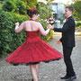 Brautkleid aus leuchtend roter Dupion-Seide und mit Perlen bestickter Spitze. Dazu passender Haarschmuck und Schuh-Clips aus der Dupion-Seide