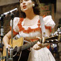 Kitty Wells sporting a darling puffed sleeve polka dot dress as she belts out at tune at The Grand Old Opry.
