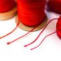 糸について。赤といっても朱か紅か、どちらの系統の色合いにするのか、光沢の有無、そして太さなど。ていねいに組合せを考えます。糸選び大好きな作業です。