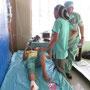 eine Patientin nach einer Operation wird vom Team bewacht