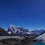 Ein Hubschrauber kommt spektakulär aus einem Gebirgstal hervorgeschossen. Im Hintergrund sind Cholatse (6440 m), Taboche (6543 m), Kangtega (6779 m) und Thamserku (6608 m)