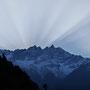 Die ersten Sonnenstrahlen schauen über den Berg