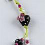 VERKAUFT! Schwarzes Herz mit weissen Pünktli und rosa Blüte an frühlingsgründem Baumwollband; Herz ca. 1,5 cm breit
