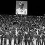Allo stadio, gli spettatori in piedi sotto un ritratto del presidente dello Zaire Mobitu, 1974 (courtesy Magnum Agency/Abbas)