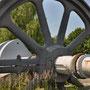 """Schwungrad mit Kurbelwelle einer Gaskolbenmaschine. Sie diente als Antrieb zur Winderzeugung eines Hochofens im ehemaligen HOESCH Hochofenwerk PHOENIX. Seit der """"Ausmusterung"""" 1980 steht es als Industriedenkmal an der TU in Dortmund - Barop"""