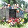 """Ein Grabstein wird gehalten von gemauerten Pflastersteinen. Die Widmung ist an die """"Söhne"""" und """"Brüder"""" gerichtet. Auch diese Stelle ist mit Blumen und zahlreichen Devotionalien geschmückt. Foto: Stefan Korinth"""