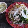 Hähnchenbruststreifen mit frischen Kräutern und Zwiebeln auf Knoblauchreis. Ein Wahnsinnsstraßensnack in Hoi An.