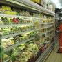 Großes Warenangebot in kleinem Supermarkt. Auffällig sind die, das Stadtbild zeichnenden, Bohrturmarbeiter in ihren bunten Overalluniformen.