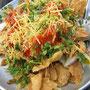Straßensnack: frittierte Getreideflakes mit Zwiebeln, Kräutern mit einem süß-sauer-scharf Dressing.