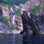 海上からしか見ることのできない『シシャモナイの滝』。まるで天然の頑強なゲートに守られているようだ。海岸で拾った黄色いヘルメットを自慢気に被っているタガメ。<積丹半島>