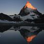 十六夜の月が黎明の空に輝く中、マッターホルンにも朝日が差して灼熱色に輝きだす。この完璧な静寂の光景を映し出す水鏡。地球の魔術は、一人の旅人のためだけに繰り広げられた。<Matterhorn-SCHWEIZ>