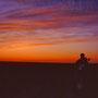 原野の中で見る夕焼けは、胸が締めつけられるほどに美しい。地平線に太陽が沈んだあとは、雲がますます燃え上がる。<道北>