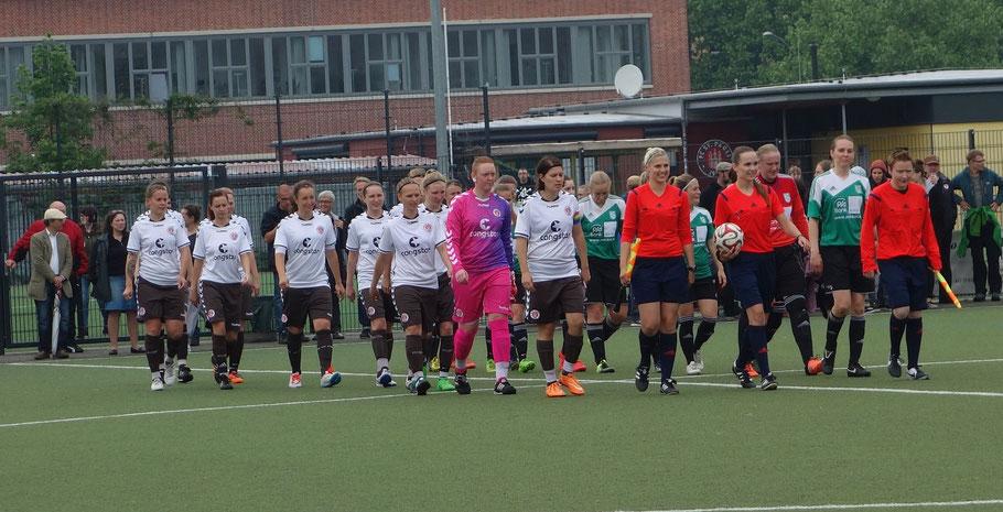 Die sehr leitende Schiedsrichterin Celina-Sophie Böhm führt die Teams auf den Platz
