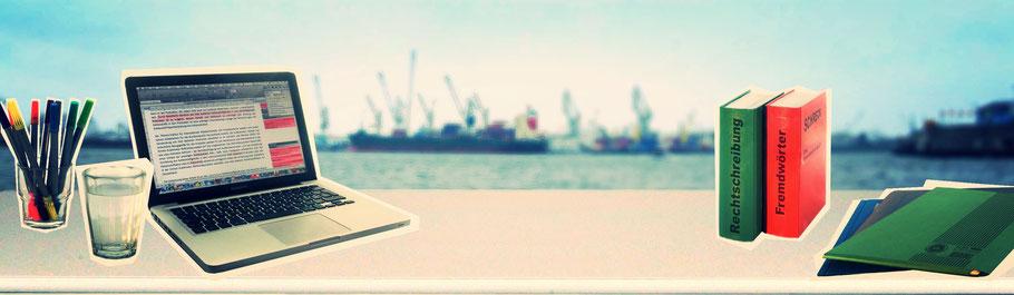 Schreibtisch mit Laptop, Stiften, Wörterbuch. Hafenkulisse im Hintergrund