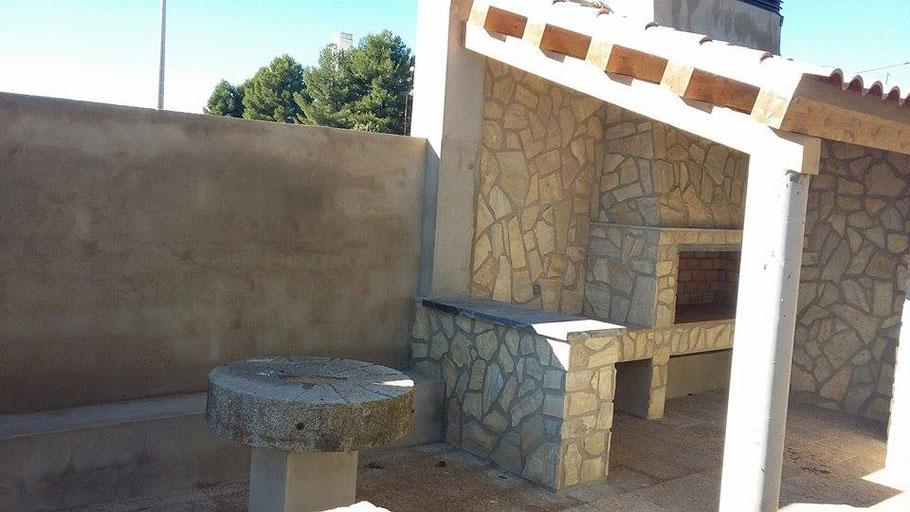 Mesa de rueda de molino de granito, antiquísima, que da carácter recio a la barbacoa.