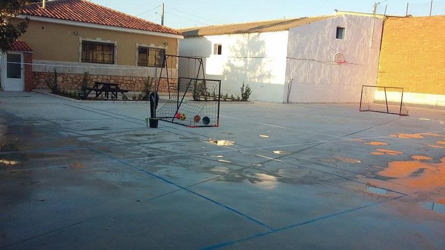 Gran pista polideportiva con porterías, donde jugar al fútbol sala, balonmano, hockey.....Con porterías portátiles. El frontón al fondo.