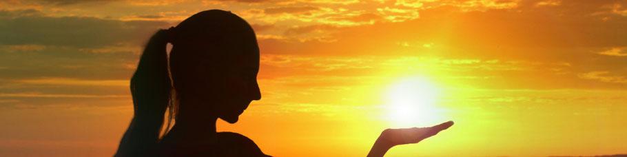 Frau vor Sonnenuntergang hält die Sonne vermeintlich in der Hand.