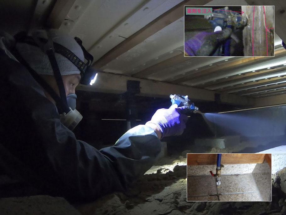 床下で薬剤散布する作業員