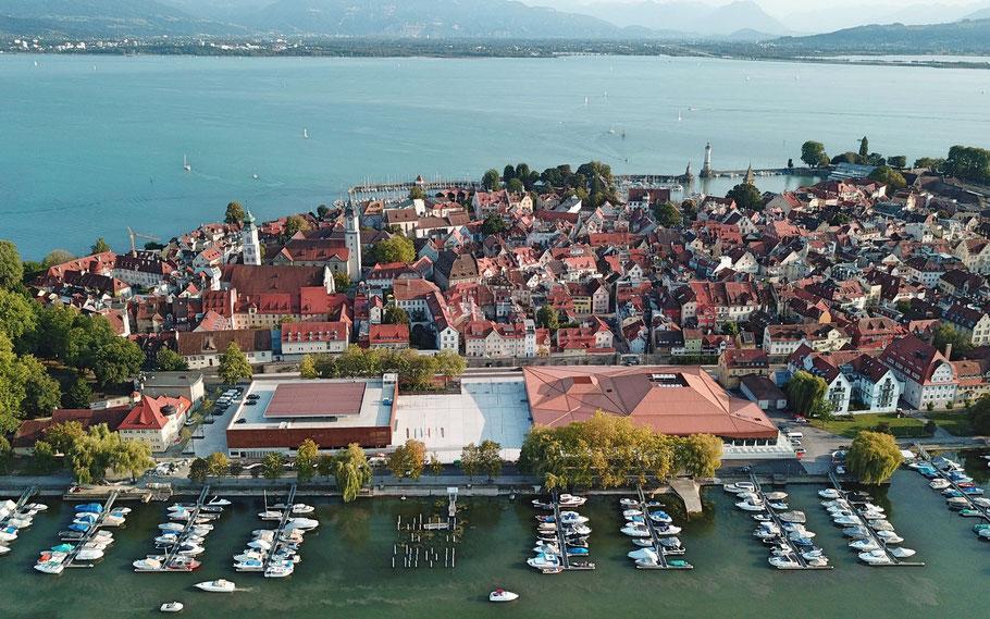 Blick aus der Vogelperspektive auf die Lindauer Insel. Im Vordergrund ist der noch relativ neue Bau der Inselhalle zu sehen. Im Hintergrund die Nachbarländer Österreich und Schweiz.