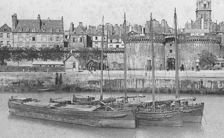 Trois chalands de Rance au mouillage  dans le bassin à marée de Saint-Malo, le premier n'a pas de gréement, il se fait certainement remorquer par un petit vapeur