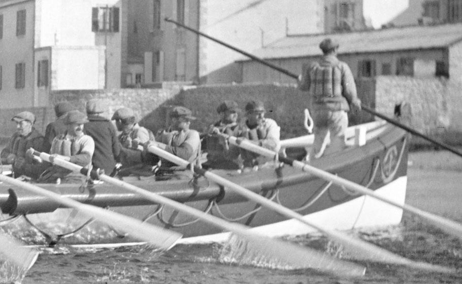 Les deux marins sauvetés de la Corentine sont assis au milieu du canot tourné vers l'avant, le sous patron déhale avec sa gaffe