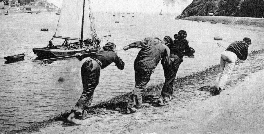 Au Légué, port de Saint-Brieuc, 4 hommes déhalent un navire sortant, un petit métier permettant aux moins aisés trainant sur le port de gagner quelques sous. Le sloup de cabotage au second plan se déhale à la godille.