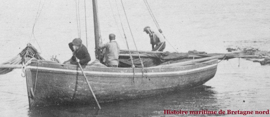 Le bateau vient de quitter la cale,  un matelot fait tourner le bateau en poussant  avec la gaffe un autre matelot  est prêt à hisser la grand-voile avec les deux drisses le patron a préparé la grand-voile et va passer de l'autre côté des espars