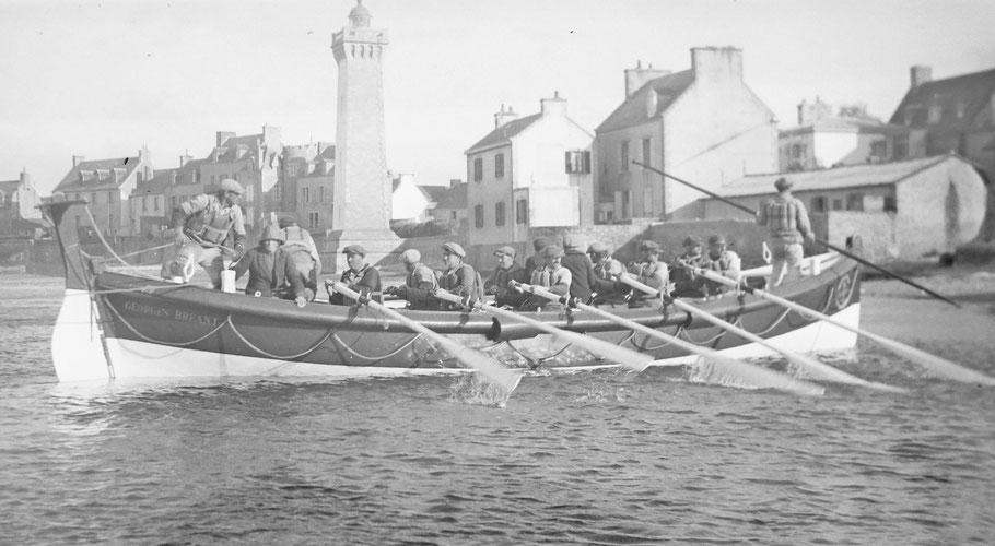 Le canot arrive à l'échouage au fond du port de Roscoff à proximité de l'abri du canot Philippes de Kerhallet et de l'abri du marin, le sous patron a la grande gaffe en main