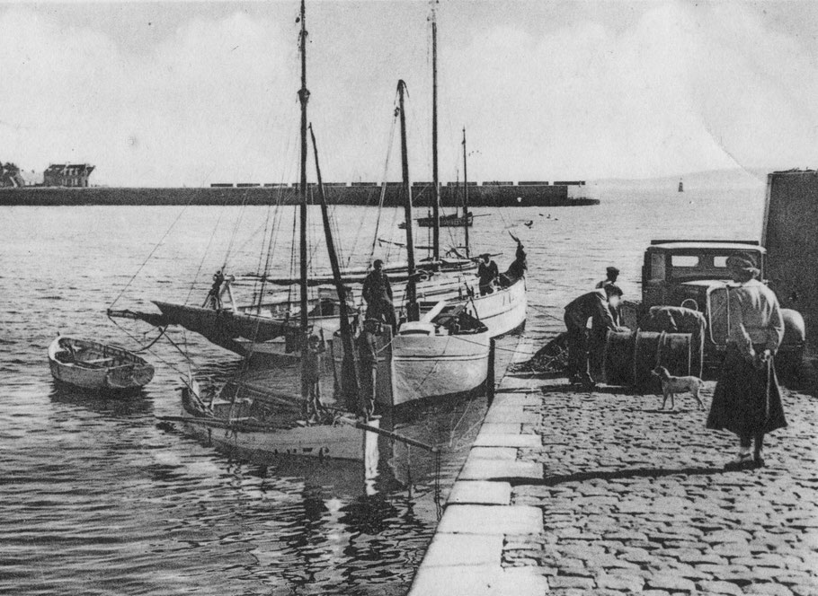 Perros Guirec cale de la douane appelée aussi cale Bitousse dans les années 30,  certains bateaux de pêche sont motorisés d'autre sont toujours uniquement à la voile, le cotre au premier plan est plein d'eau !