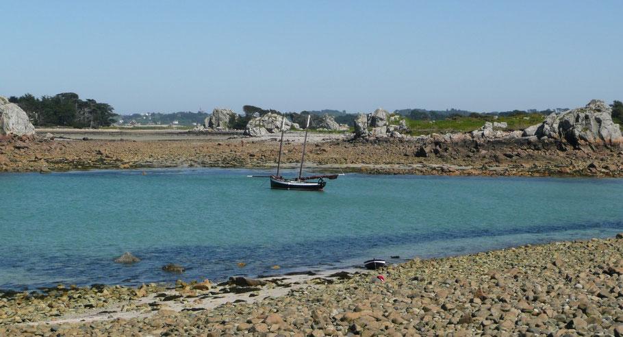 Ar Jentilez, réplique de flambart goémonier de Perros, au mouillage au Port-Noir, au second plan, de gauche à droite, l'île Zilliec, la roche aux cochons, les îles Gouinisis