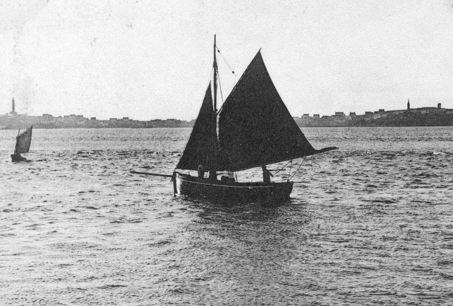 Sloup de passage dans le chenal, l'équipage est de deux personnes, le patron à la barre et un matelot à l'avant, deux femmes de l'île en coiffe sont assises sur le banc du milieu