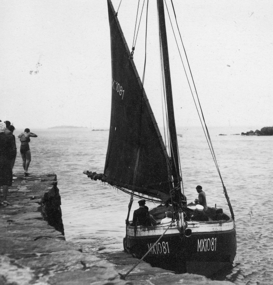 Le Coq de l'île au Vil dans les années trente, une baigneuse en maillot s'apprête à plonger  du petit quai, les passagers sont à bord et c'est certainement Saïk Le Saout dit l'Amiral qui est à la barre
