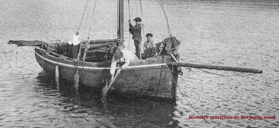 Vers 1903 au port du vil à Roscoff une ilienne en coiffe est assise sur le banc les défense semble être de simples morceaux de bois