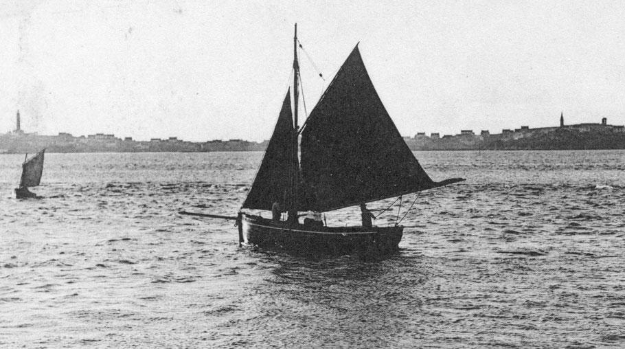 Le courrier de l'île de Batz dans le chenal vers 1903 à bord le patron à la barre un matelot en avant du mât et deux iliennes en coiffe au milieu du bateau ( Coll personnelle)