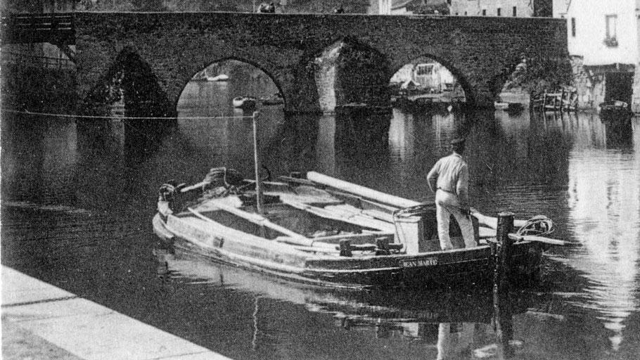 """En aval du vieux pont de Dinan, le petit chaland de Rance """"Jean-Marie"""" est déhalé à la cordelle avec un mâtereau, son mât et sa voile pour la navigation en estuaire sont posés en abord. Cette technique semble universelle ; seul le vocabulaire change."""